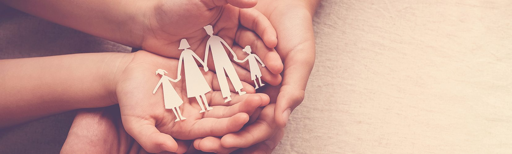 Bild Quelle: AdobeStock_282163930_©sewcream _hands holding paper family cutout, family home,life insurance, adoption foster care